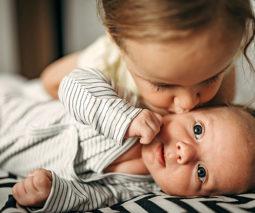 Toddler girl kissing newborn sibling - feature