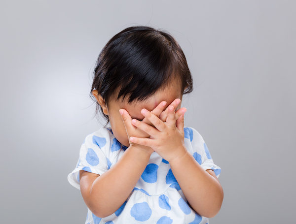 Toddler with hands over face