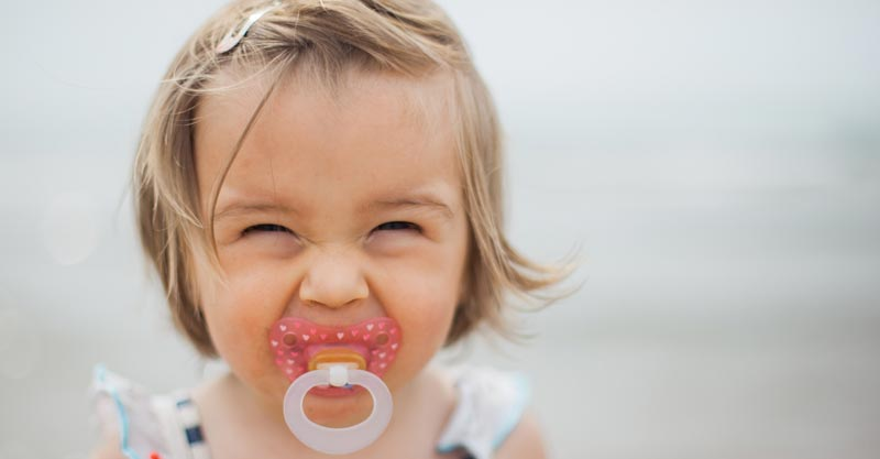 Happy toddler with dummy in mouth