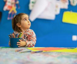 Preschool girl holding bucket of crayons - feature