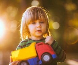 Toddler boy holding toy dump truck - feature