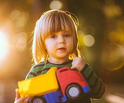 Toddler boy holding toy dump truck - thumbnail