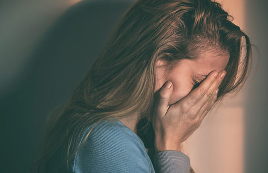 Upset woman crying with hands covering face