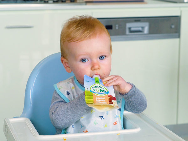 Baby boy sitting in highchair eating a baby food pouch