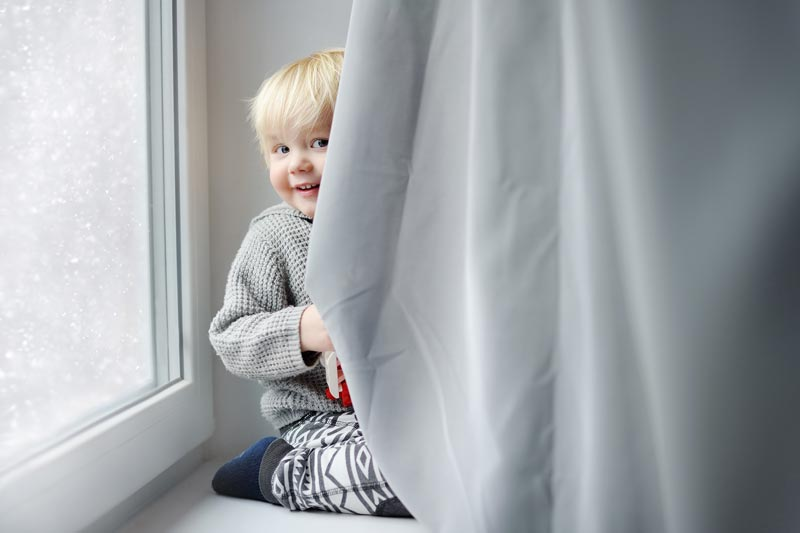 Toddler hiding behind curtain