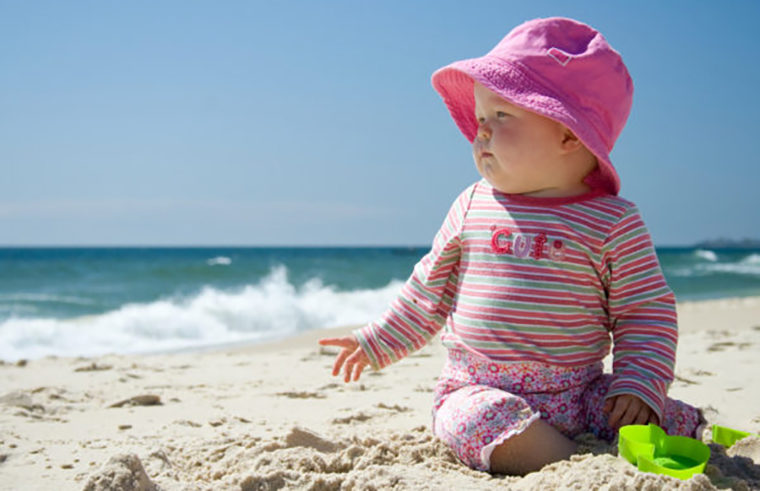 Baby on beach wearing hat and rashie - feature