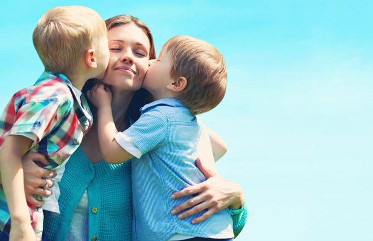 Two boys kissing mother and hugging - feature