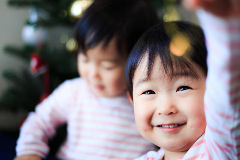 Asian toddlers looking at Christmas lights