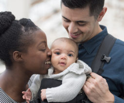 Young family with baby in baby carrier - feature