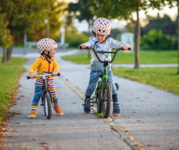 Two boys riding bikes bicycles wearing helmets - feature