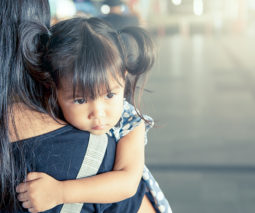 Young girl being carried by mother looking sad - feature