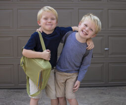 Twin boys smiling and holding a school bag - feature
