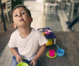 Young boy sitting in cafe with toys sticking tongue out - feature