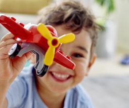 Young boy playing with a Lego Duplo plane