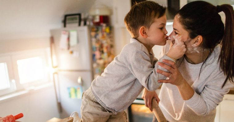 Mother and young boy kissing inside