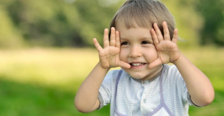 Preschool child holding hands up to face and smiling