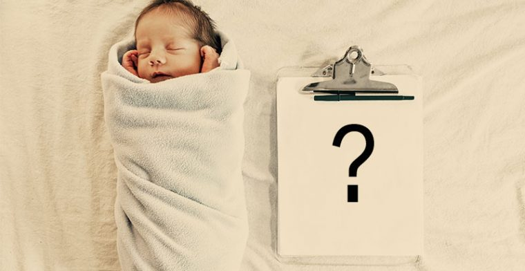 Baby wrapped lying next to clipboard - baby names