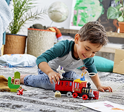Young boy playing with a toy train on carpet
