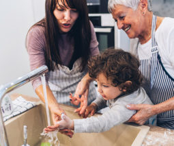 Mother and grandmother helping toddler to wash hands - feature