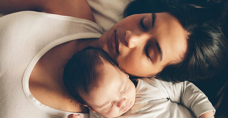Mother sleeping with newborn baby cuddled in