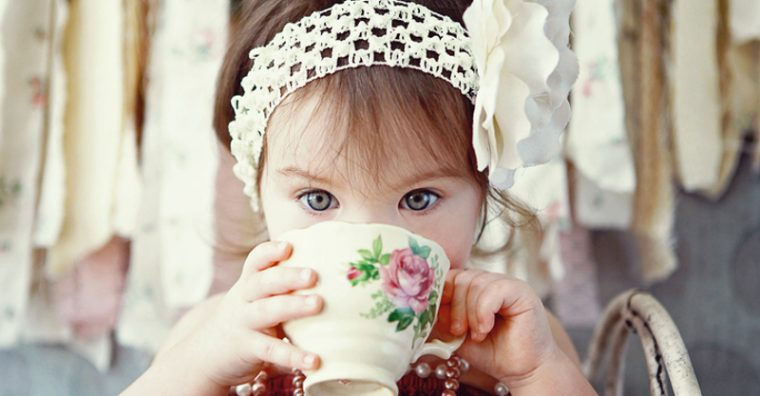 Toddler girl drinking from porcelain cup