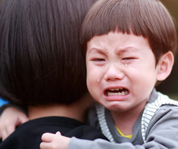 Asian toddler crying on mum's shoulder