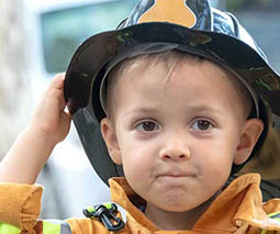 Young boy in fireman hat and coat