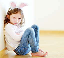 angry young girl with easter bunny ears on her head