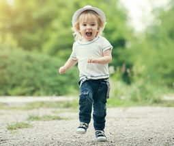 toddler boy in hat running on path