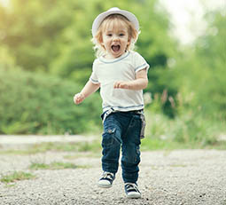toddler boy running in garden