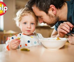 Dad leaning into toddler eating dinner