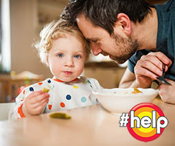 Father feeding toddler at table.