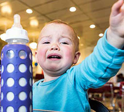 crying toddler boy with bottle