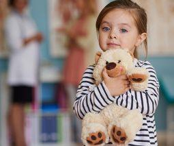 Child hugging teddy in hospital