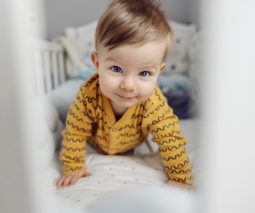 Baby in cot looking through bars - feature