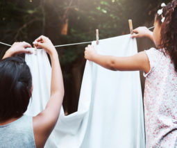 Mother and daughter hanging washing on clothes line