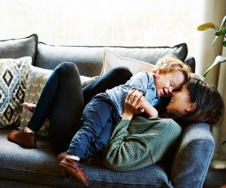 Mother lying on couch playing with toddler boy in her arms