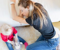 Tired mum resting on couch with toddler