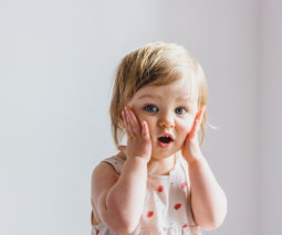 Surprised toddler girl with hands on cheeks - feature