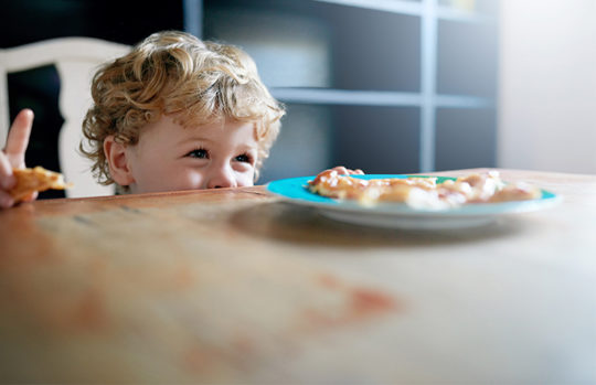 Toddler boy looking at dinner on kitchen table - feature