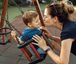Mother pushing child on swing giving him a kiss