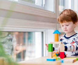 toddler at window playing with blocks