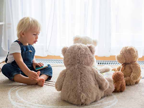 Toddler boy sitting on floor reading to his teddy bears