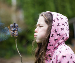 Girl blowing roasted marshmallow - camping