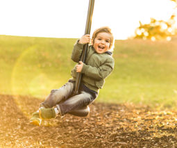 Toddler boy playing on swing at the park
