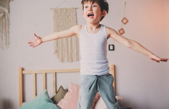 Preschool boy jumping on bed feature