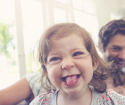 Cheeky toddler girl sticking her tongue out feature