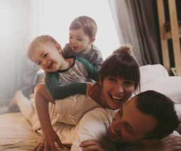 Young family laughing in bed together feature