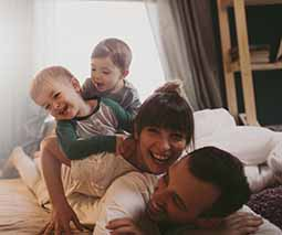 Young family playing together in bed thumbnail