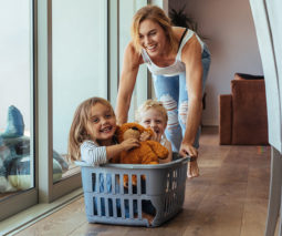 Mother pushing her children in laundry basket playing feature